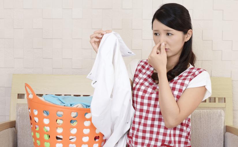 洗濯物のニオイが臭くて鼻をつまむ女性